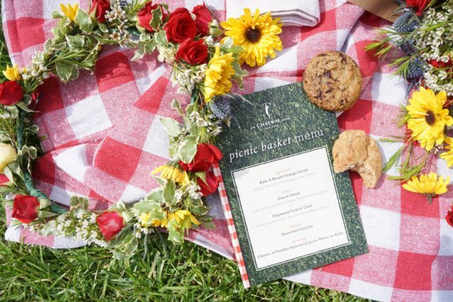Picnic blanket with flowers, cookies, and picnic menu
