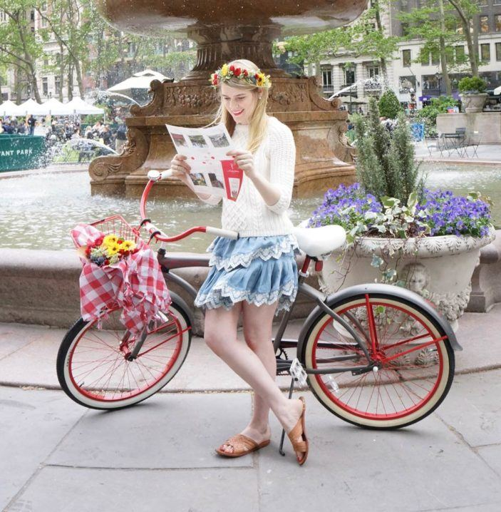 A blonde haired woman with a flower crown leaning against a vintage bicycle reading a pamphlet in front of a large fountain