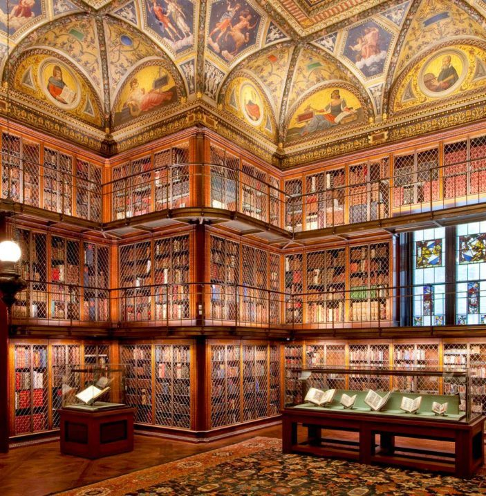 Large room with three stories of book lined walls with decorative ceiling