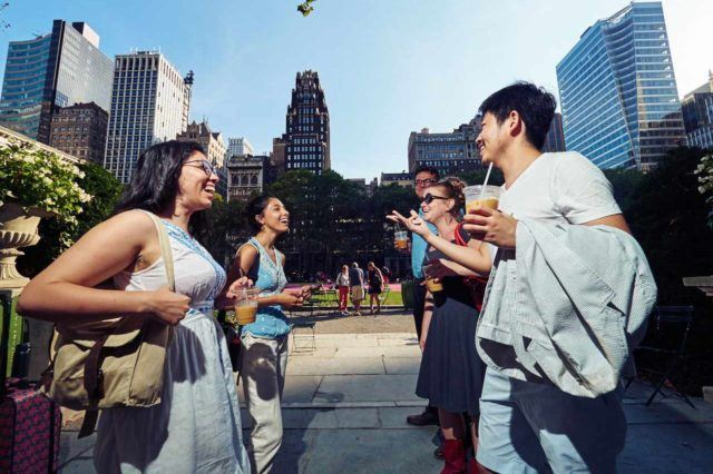 Five adults laughing and conversing outdoors in a city park against tall buildings and a blue sky