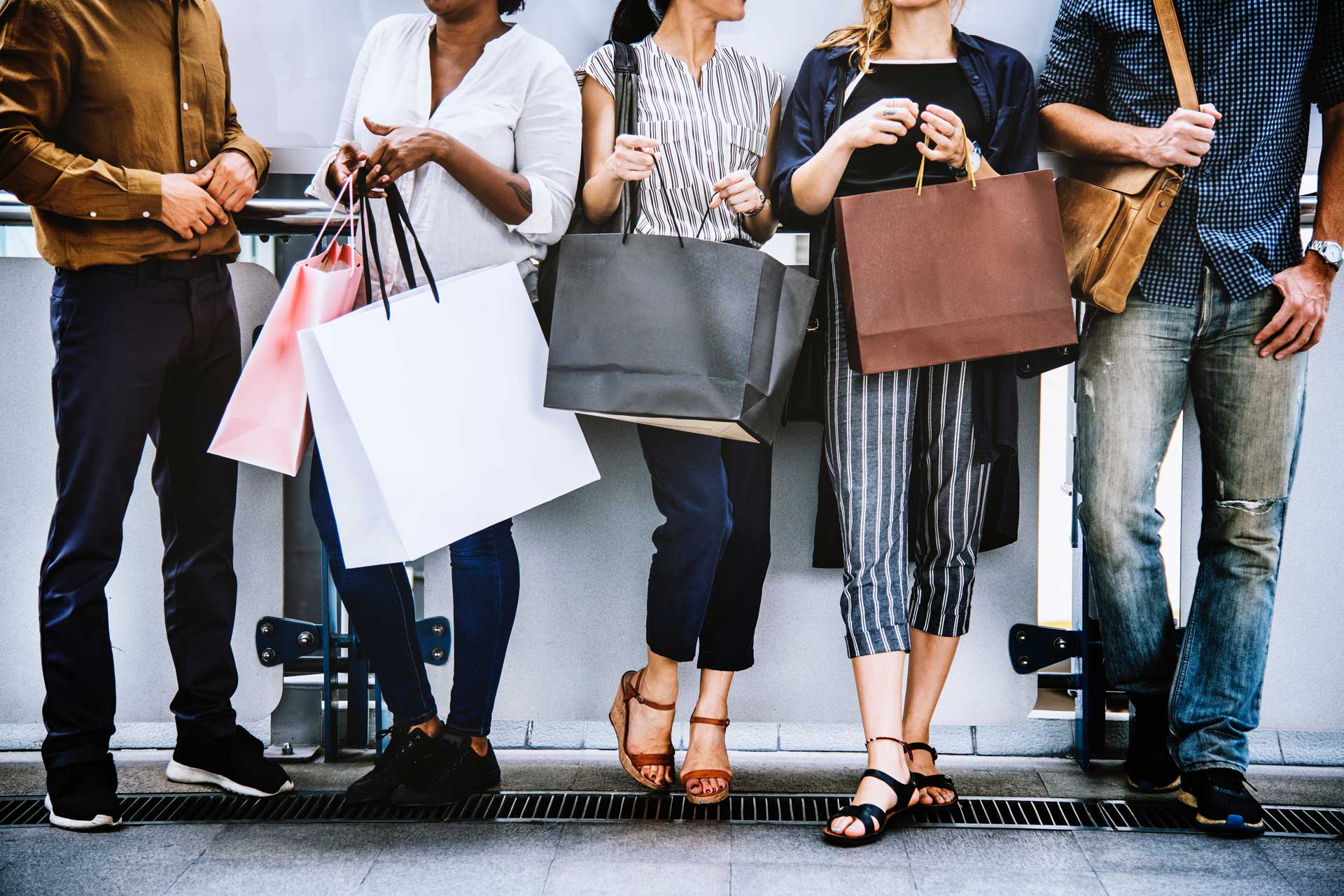group of friends standing against wall holding shopping bags