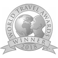 A white and grey circular logo with a man holding the earth in the center for 2017 World Travel Awards Winner