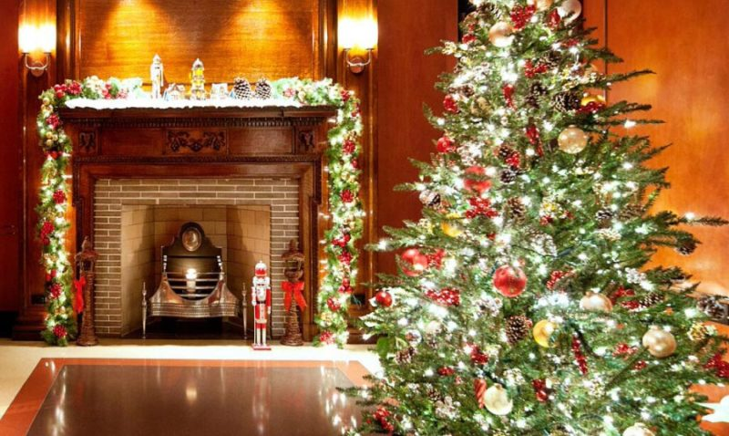 Brightly lit and decorated Christmas tree with fireplace in the background
