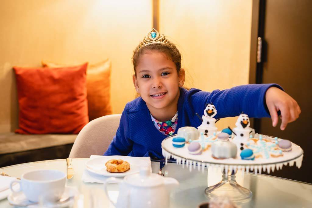 young girl smiling happily while snacking on Frozen movie themed desserts while wearing a crown