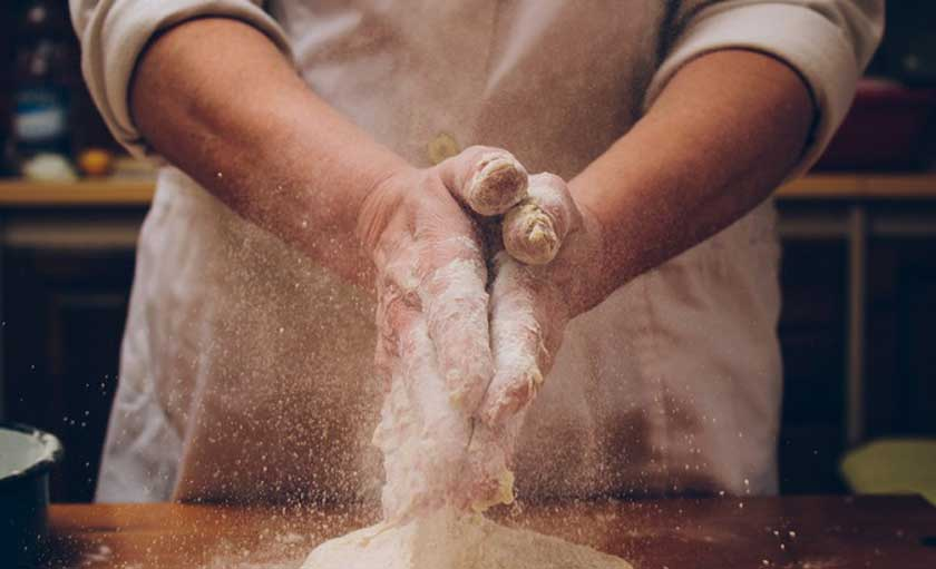 man making dough with flower all over his hands