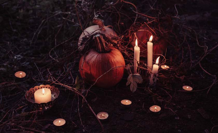 pumpkins surrounded by candles