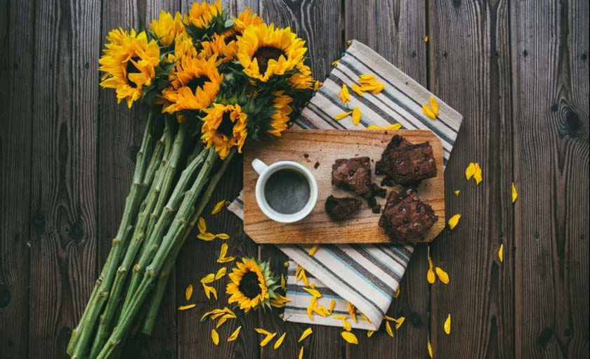 sunflowers laying on wood with a display of brownies and coffee next to them
