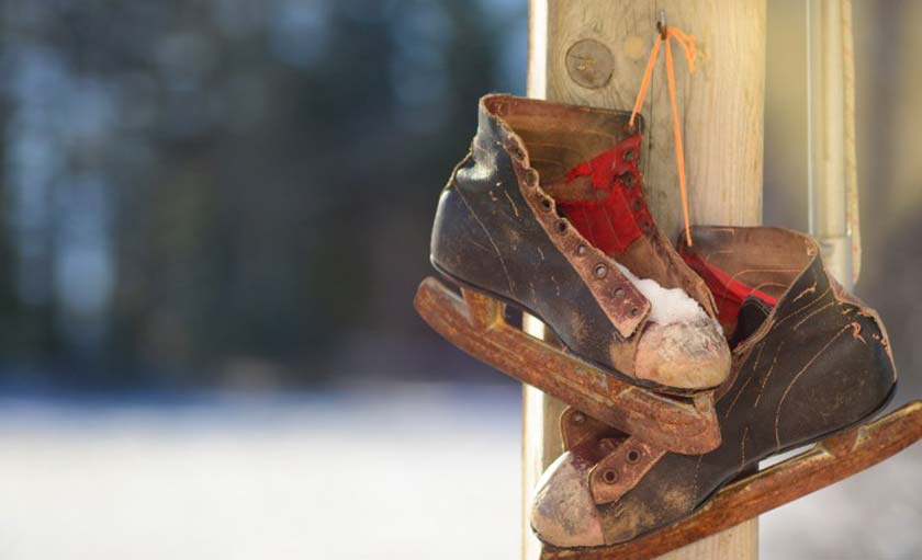 old ruined skates hanging on a hook on a piece of wood
