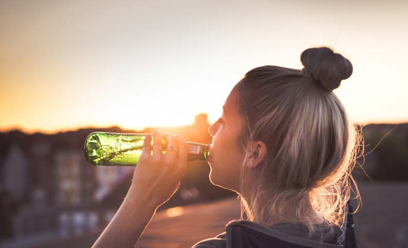 woman drinking out of a green beer bottle