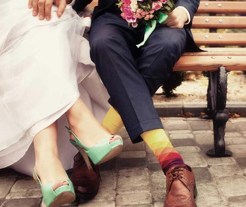 torso down shot of bride and groom sitting on wooden bench with grooms hand placed on brides knee