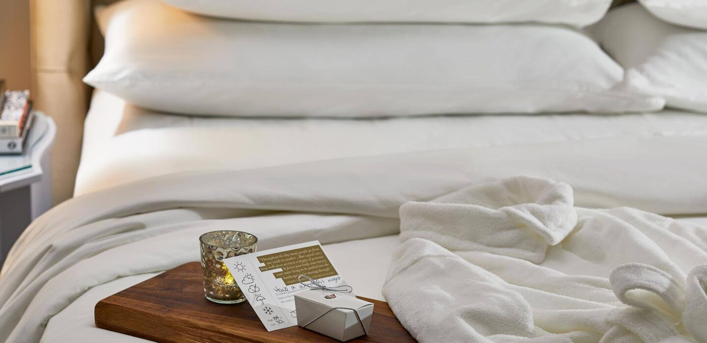 a smooth wood board sitting on a hotel room bed with a note, a gift box, and a candle on top