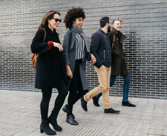 Full length of cheerful friends in trendy clothes strolling along urban street against black brick wall at daytime.