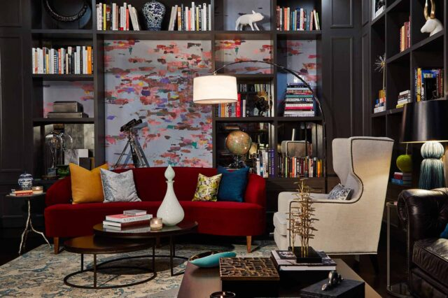 An eclectic sitting room in a luxury hotel with an elegant red couch and beige chair and many shelves of books