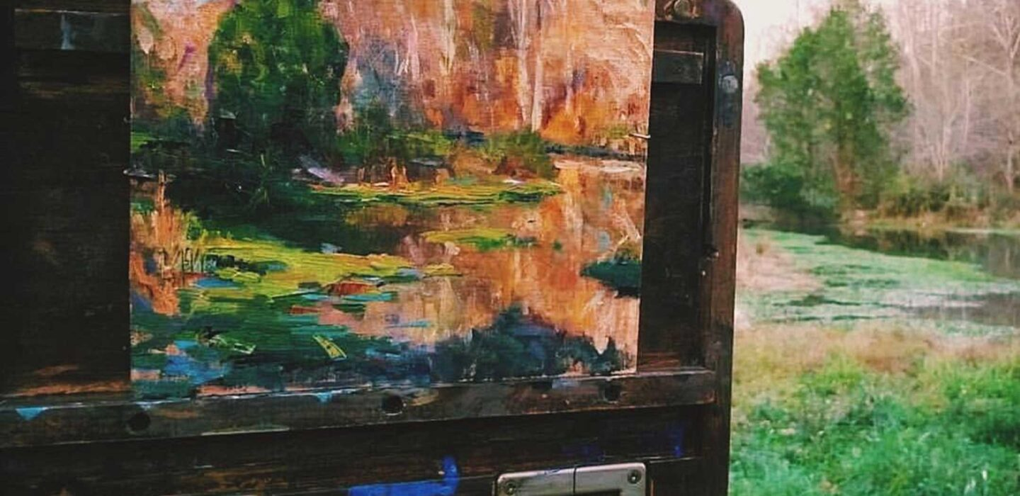 painting of nature on an easel in the woods