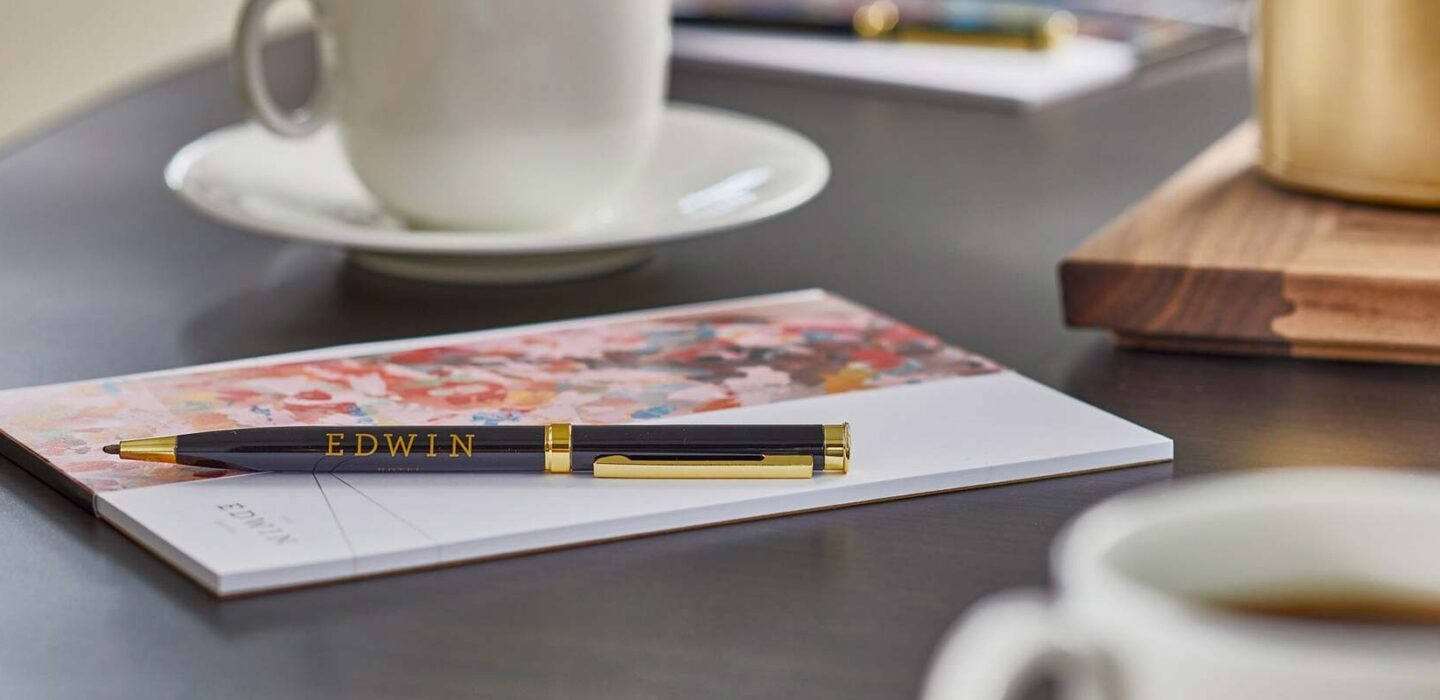 black pen on top of a notepad surrounded by white mugs of coffee