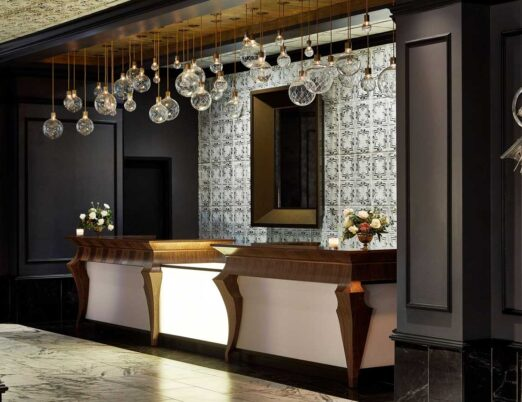 dark hotel lobby front desk with gold accents, a white fireplace, large mirror, and large glass light fixture