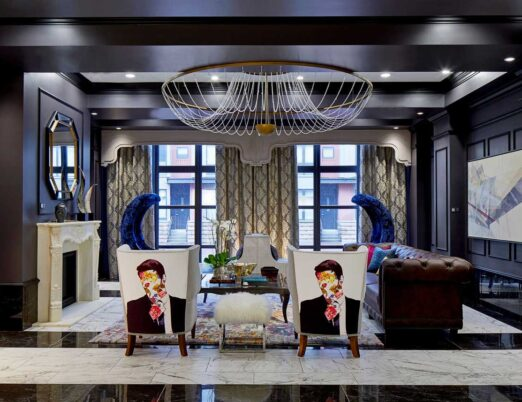 dark hotel lobby with gold accents, a white fireplace, large mirror, and large gold chandelier