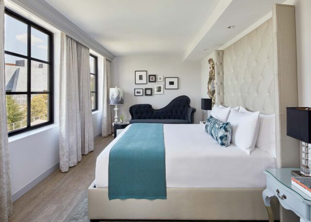 A long luxury hotel room with king bed with white linens, two large windows, and a plush day bed
