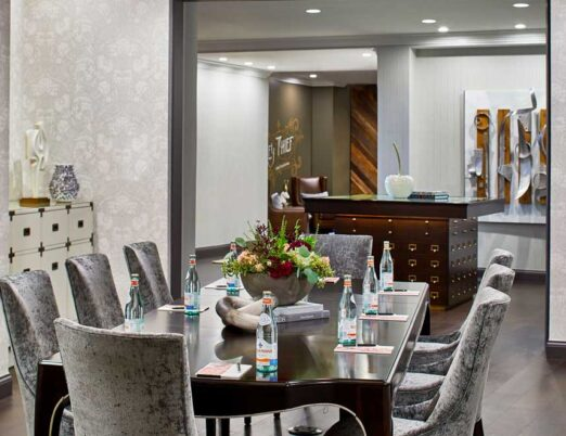 luxury meeting room with a large brown table surrounded with grey suede chairs