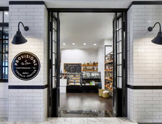 white brick entrance to a snack shop with black doors
