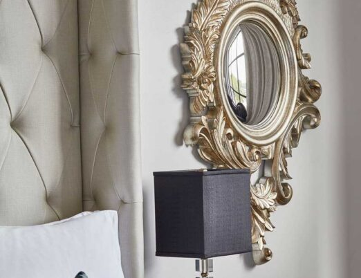 bright hotel room side table with a black table lamp on it and a gold mirror next to it