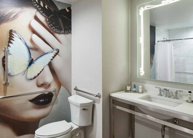 a hotel bathroom with a full wall art piece featuring a woman's face and a butterfly