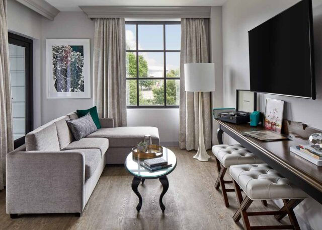 Luxury hotel living room suite with a sectional sofa, flat screen tv, and large window
