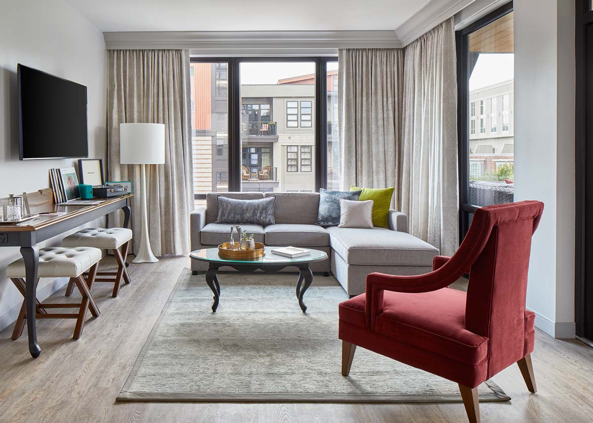 Luxury hotel living room suite with a sectional sofa, red plush chair, flat screen tv, and large windows