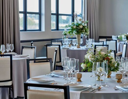 bright wedding venue room filled with tables and chairs with flower bouquet centrepieces on each table