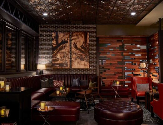dark leather booth with an ottoman and candles surrounding it, with brown brick walls with brown artwork on them