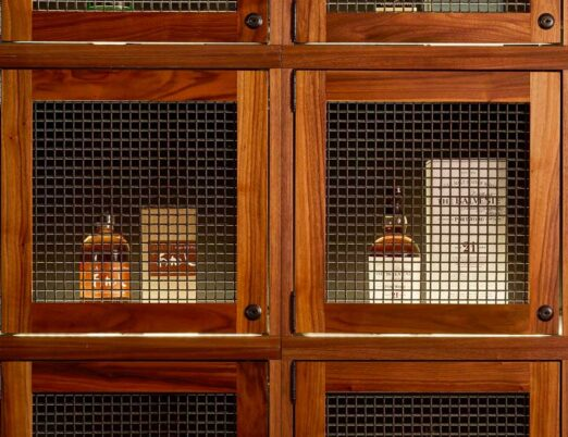 wooden display case with bottles of alcohol inside