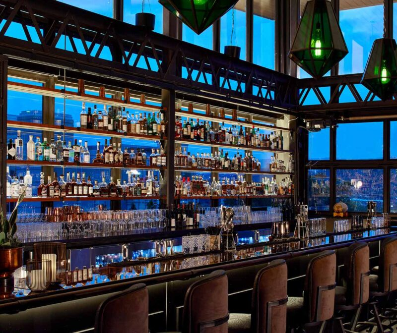 an indoor roof top bar with dozens of bottles, and green pendent lights surrounded by floor-to-ceiling windows