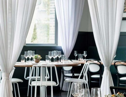bright restaurant with white curtains, white chairs, and wooden tables with glasses and flowers on them