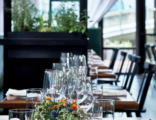 wooden tables covered with cutlery, plates, and glasses as well as a plant as a centrepiece