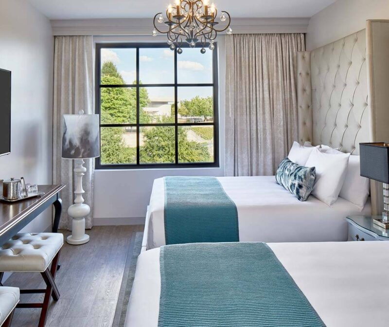A luxury hotel room with two double beds, chandelier, flat screen tv, and a large window