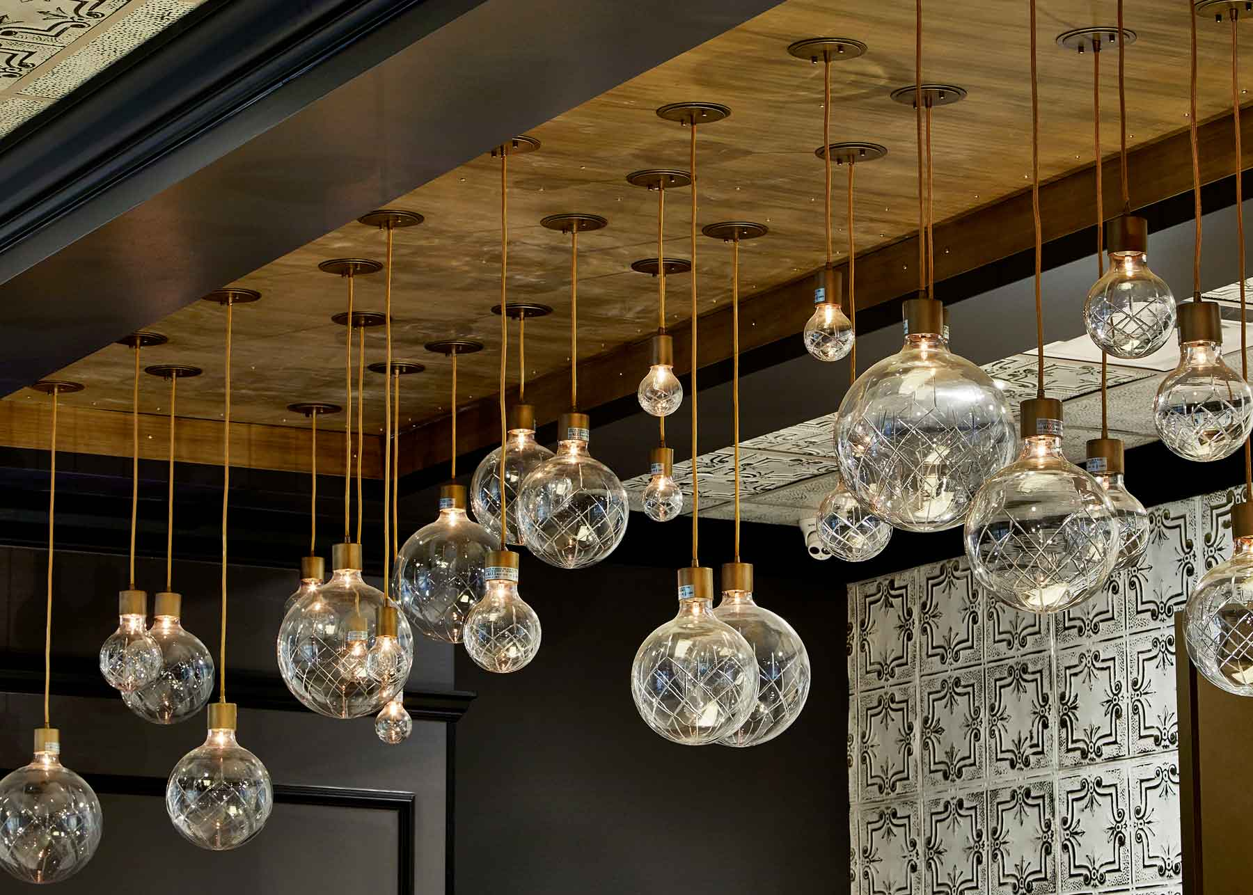 Many ornate crystal globe lights of different sizes hang from a wood toned ceiling