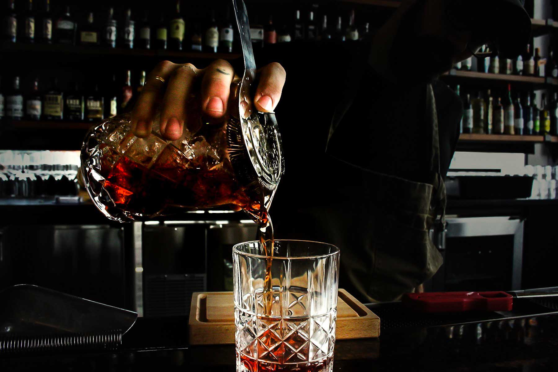 a bartender pouring a cocktail through a strainer into a crystal glass