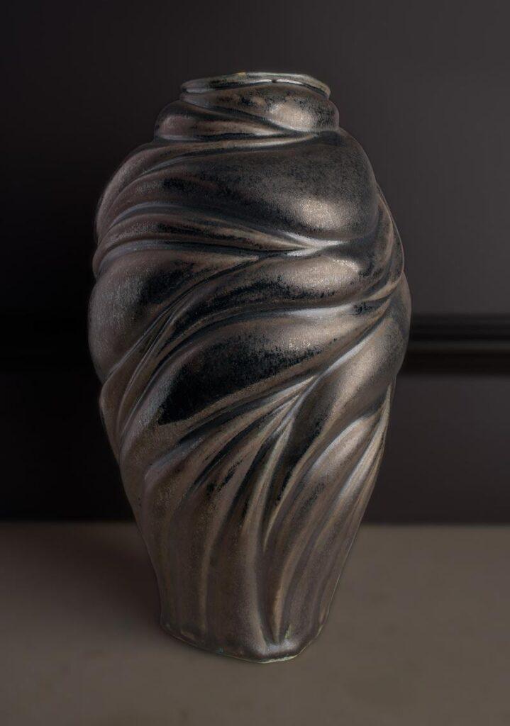 dark vase displayed on a black wall
