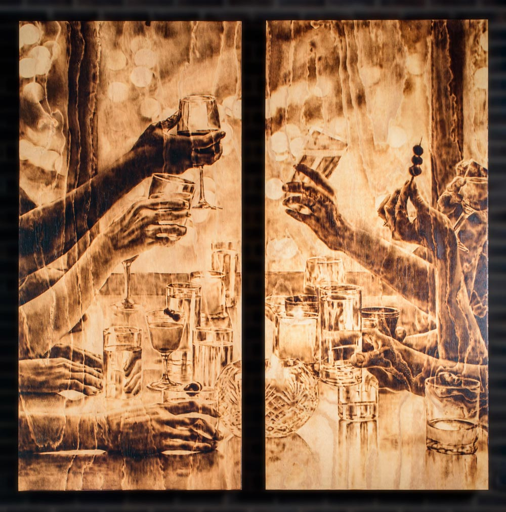 burned wood artwork of people holding up their glasses at a table