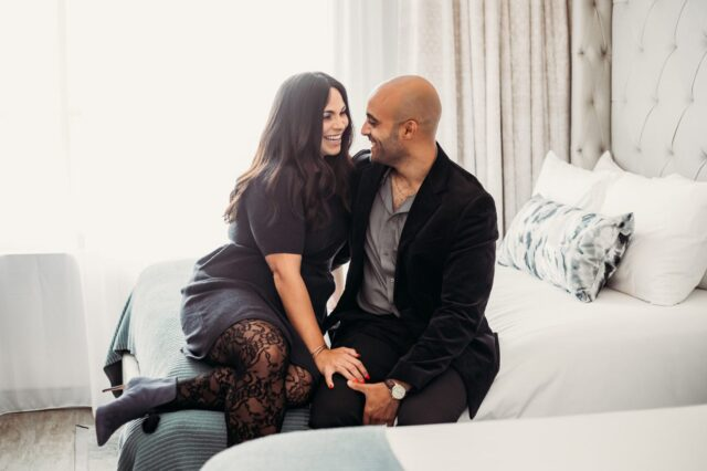 couple smiling while sitting on hotel bed with one another