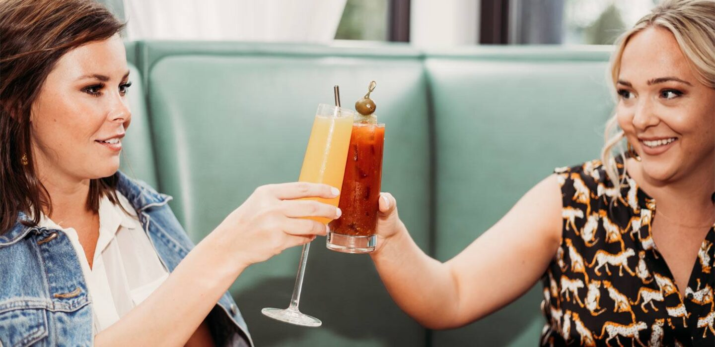 two friends clinking their two cocktails together in celebration