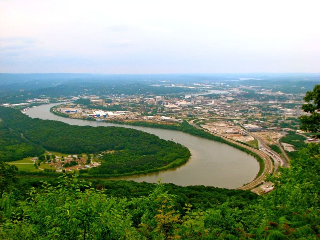 distant city surrounded by trees and a large river
