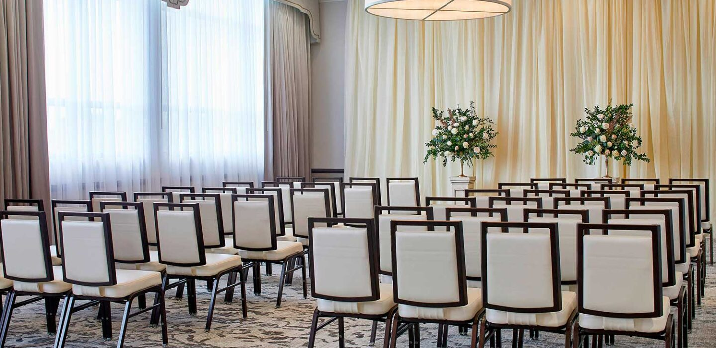 conference room with rows of brown and white chairs with curtains on each wall and two flower arrangements at the front of the room
