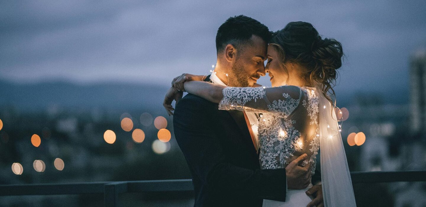 bride and groom hugging outdoors with fairy lights wrapped around them