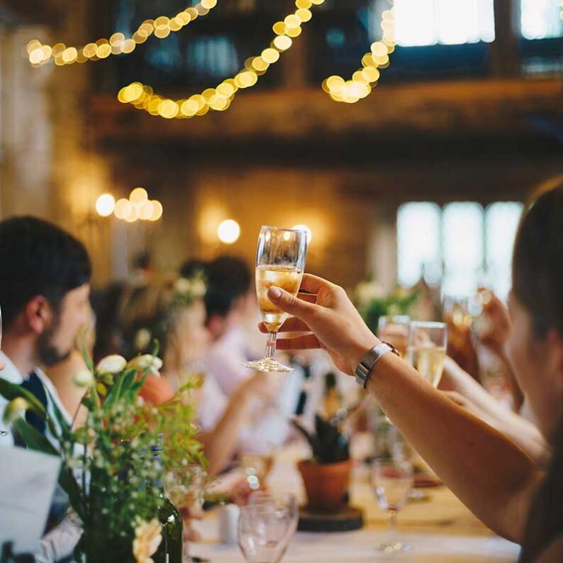 people sitting at a large table holding up champagne glasses