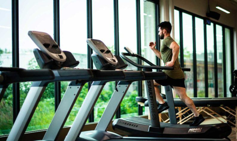 man wearing green crew-neck shirt using treadmill