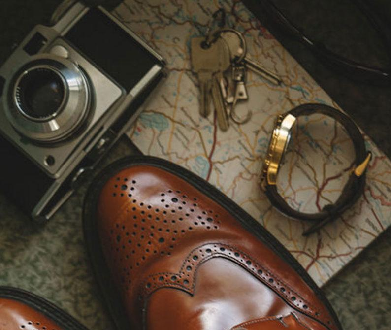 pair of brown wingtip leather shoes besides gray point-and-shoot camera