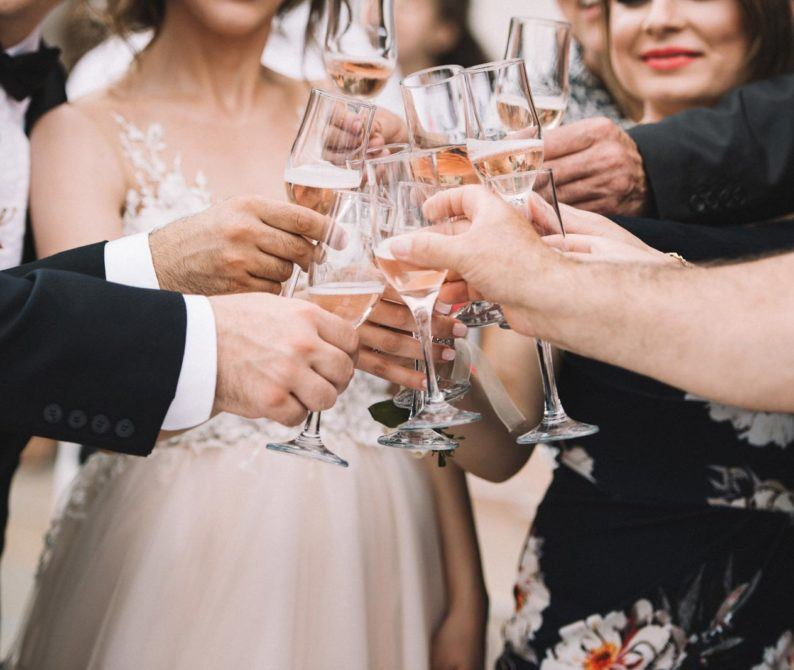 bride, groom and friends toasting clear wine glasses