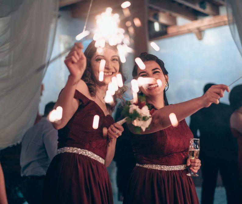 smiling women holding sparklers during wedding celebration