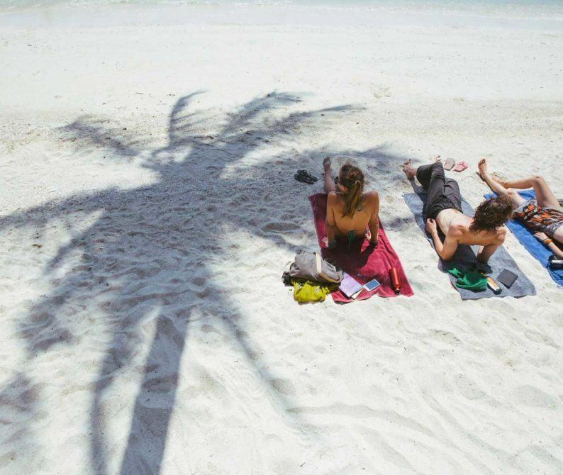 three person lying on towels on the sandy beach
